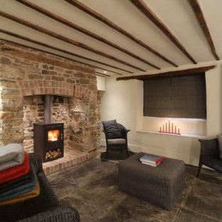 Esempio di un piccolo soggiorno country aperto con pavimento in pietra calcarea, stufa a legna e cornice del camino in pietra