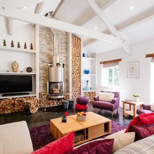 Photo of a country open concept living room in Cornwall with white walls, a wood stove, a wall-mounted tv and black floor.
