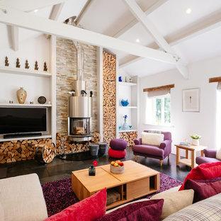 Imagen de salón abierto, de estilo de casa de campo, con paredes blancas, estufa de leña, televisor colgado en la pared y suelo negro