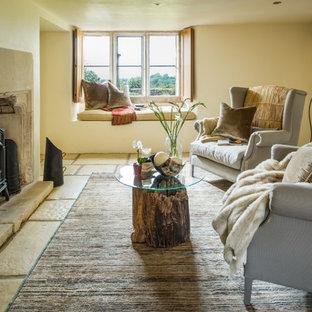 Imagen de salón para visitas cerrado, campestre, de tamaño medio, con paredes amarillas, suelo de piedra caliza, estufa de leña, marco de chimenea de piedra y suelo beige