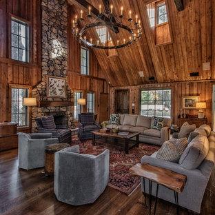 Repräsentatives, Fernseherloses, Offenes Uriges Wohnzimmer mit brauner Wandfarbe, dunklem Holzboden, Kamin, Kaminsims aus Stein und braunem Boden in Sonstige