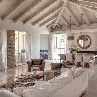 Modelo de salón para visitas abierto, mediterráneo, de tamaño medio, con suelo de piedra caliza, estufa de leña y marco de chimenea de metal