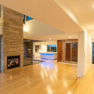Idee per un grande soggiorno contemporaneo aperto con pareti bianche, pavimento in bambù, camino bifacciale, cornice del camino piastrellata e nessuna TV
