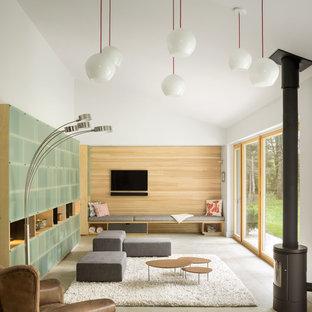 ポートランド(メイン)の中サイズのコンテンポラリースタイルのおしゃれなリビング (白い壁、コンクリートの床、薪ストーブ、壁掛け型テレビ) の写真