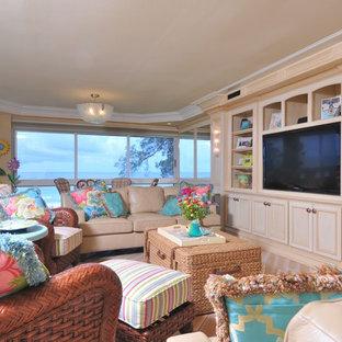 Ispirazione per un ampio soggiorno tropicale aperto con pareti gialle, parquet chiaro, nessun camino e parete attrezzata