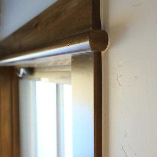 デンバーの大きいラスティックスタイルのおしゃれなLDK (白い壁、カーペット敷き、コーナー設置型暖炉、石材の暖炉まわり、据え置き型テレビ、白い床) の写真
