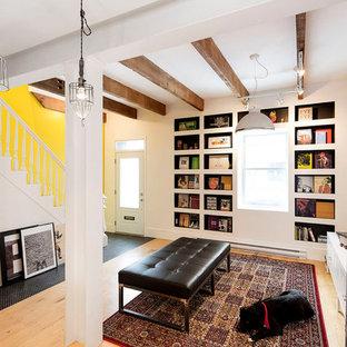 Immagine di un piccolo soggiorno country aperto con libreria, pareti gialle, parquet chiaro, nessun camino e nessuna TV