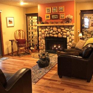 他の地域の中サイズのラスティックスタイルのおしゃれなLDK (オレンジの壁、無垢フローリング、標準型暖炉、石材の暖炉まわり、テレビなし) の写真