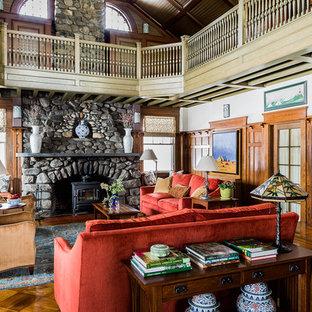 Immagine di un grande soggiorno american style aperto con pareti beige, pavimento in legno massello medio, camino classico, cornice del camino in pietra e TV nascosta