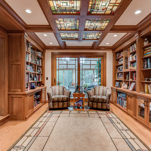 Example of a large arts and crafts open concept light wood floor living room library design in Chicago with beige walls and no tv