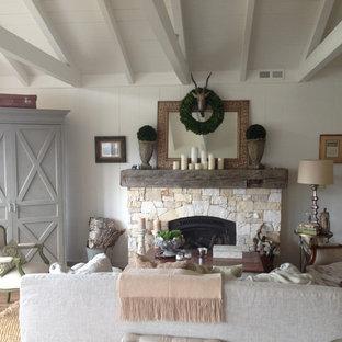 Idee per un soggiorno american style di medie dimensioni e aperto con sala formale, pareti bianche, pavimento in legno massello medio, camino classico, cornice del camino in pietra, nessuna TV e pavimento marrone