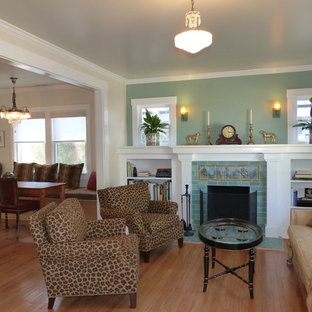 Design ideas for a mid-sized arts and crafts open concept living room in Santa Barbara with green walls, light hardwood floors, a standard fireplace, a tile fireplace surround and no tv.
