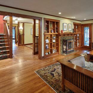 Immagine di un soggiorno stile americano di medie dimensioni con pavimento in legno massello medio, camino classico, cornice del camino piastrellata e pareti gialle