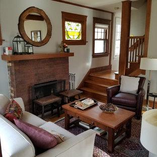 Esempio di un soggiorno american style di medie dimensioni e aperto con sala formale, pareti bianche, parquet chiaro, camino classico, cornice del camino in mattoni, nessuna TV e pavimento beige