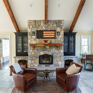 Foto di un soggiorno american style di medie dimensioni e aperto con pareti beige, camino classico, cornice del camino in pietra, pavimento in ardesia e pavimento marrone