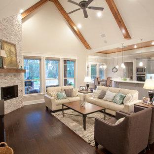 Modelo de salón abierto, de estilo americano, grande, con paredes beige, suelo de madera oscura, chimenea de esquina, marco de chimenea de piedra y suelo marrón