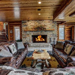 Modelo de salón para visitas abierto, rural, sin televisor, con paredes marrones, chimenea lineal y marco de chimenea de piedra