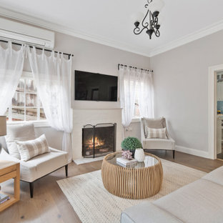 Design ideas for a transitional enclosed living room in Other with grey walls, medium hardwood floors, a standard fireplace, a brick fireplace surround and brown floor.