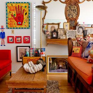 Ejemplo de salón para visitas abierto, bohemio, de tamaño medio, sin chimenea y televisor, con paredes blancas, suelo de madera en tonos medios y suelo marrón