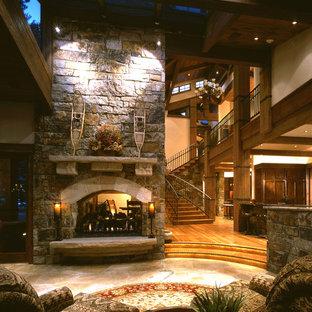 Ispirazione per un grande soggiorno rustico aperto con sala formale, pareti beige, pavimento in travertino, camino bifacciale, cornice del camino in pietra e pavimento marrone