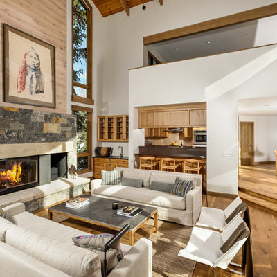 Inspiration for a mid-sized rustic formal and open concept medium tone wood floor living room remodel in Denver with white walls, a standard fireplace, a stone fireplace and no tv