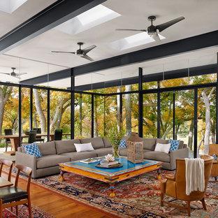 Diseño de salón para visitas abierto, moderno, grande, con paredes blancas, suelo de madera en tonos medios, marco de chimenea de piedra y televisor colgado en la pared