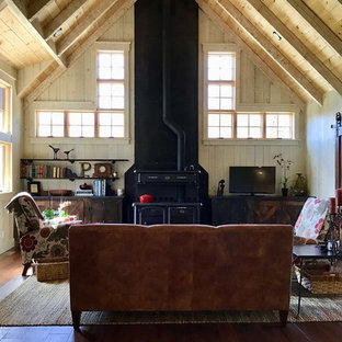 Inspiration for a mid-sized cottage open concept dark wood floor and brown floor living room remodel in Other with beige walls, a wood stove and a tv stand