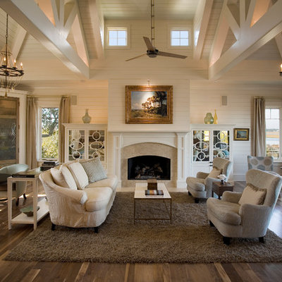 Example of a beach style open concept medium tone wood floor living room design in Charleston with white walls