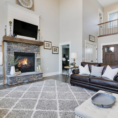 Large country formal and open concept medium tone wood floor and brown floor living room photo in Grand Rapids with gray walls, a standard fireplace, a stone fireplace and a wall-mounted tv