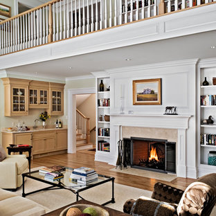 Example of a cottage living room design in New York with beige walls and a standard fireplace