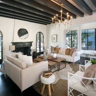 Modelo de salón para visitas cerrado, mediterráneo, grande, sin televisor, con paredes blancas, suelo de madera oscura, chimenea tradicional, marco de chimenea de baldosas y/o azulejos y suelo negro