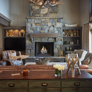Photo of a rustic open plan living room in Grand Rapids with brown walls, medium hardwood flooring, a standard fireplace, a stone fireplace surround and a built-in media unit.