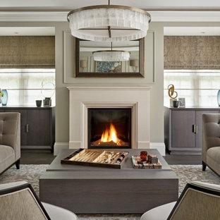 Inredning av ett modernt stort separat vardagsrum, med en standard öppen spis, en spiselkrans i sten, grå väggar, mörkt trägolv och brunt golv