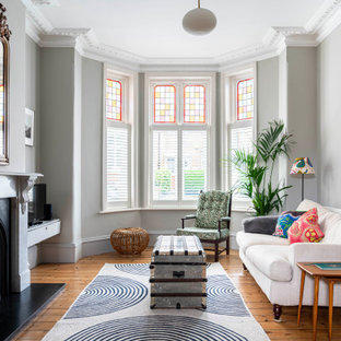 Photo of a scandinavian living room in London with grey walls, medium hardwood flooring, a standard fireplace and brown floors.