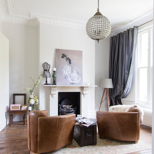 Living room - mid-sized contemporary enclosed and formal medium tone wood floor living room idea in London with white walls, a standard fireplace and no tv