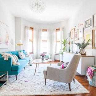 Idéer för eklektiska vardagsrum, med vita väggar, mellanmörkt trägolv, en fristående TV och brunt golv