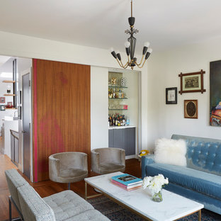 Eclectic medium tone wood floor living room photo in New York with a bar and white walls