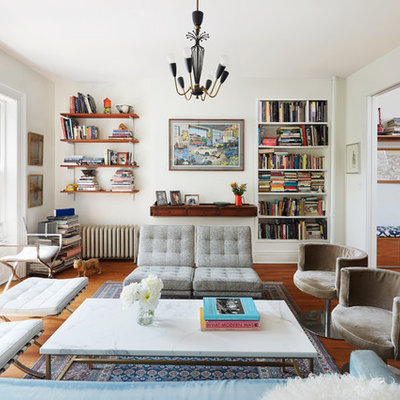 Example of an eclectic enclosed medium tone wood floor living room library design in New York with white walls