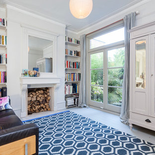 This is an example of a scandi enclosed living room in London with a reading nook, grey walls, painted wood flooring and a standard fireplace.