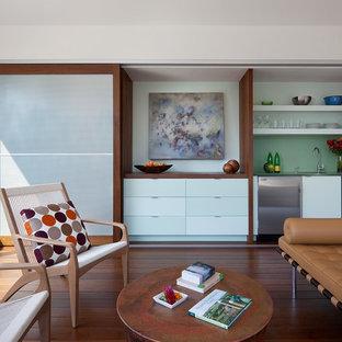 Ejemplo de salón con barra de bar abierto, minimalista, pequeño, con paredes blancas, suelo de madera oscura y televisor retractable