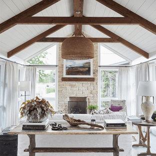 ダラスのビーチスタイルのおしゃれなLDK (コンクリートの床、標準型暖炉、石材の暖炉まわり、グレーの床) の写真