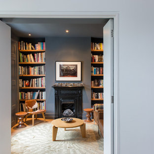Living room library - small contemporary enclosed living room library idea in London with blue walls, a standard fireplace and no tv