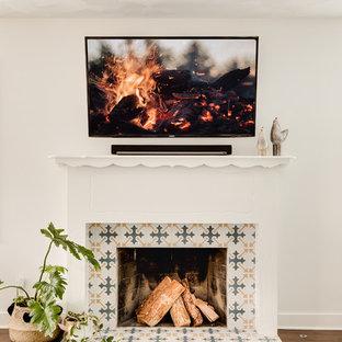 ロサンゼルスの中サイズのビーチスタイルのおしゃれなLDK (マルチカラーの壁、無垢フローリング、標準型暖炉、木材の暖炉まわり、壁掛け型テレビ) の写真