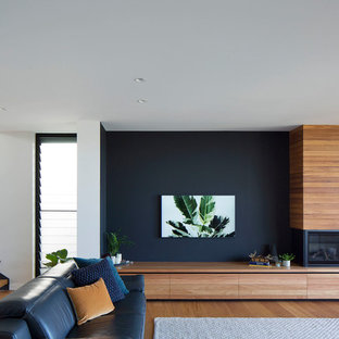 Photo of a contemporary living room in Sydney with blue walls, medium hardwood floors, a standard fireplace, a wood fireplace surround and brown floor.