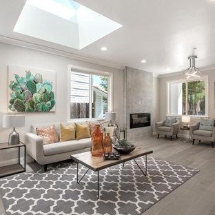 サンフランシスコの広い地中海スタイルのおしゃれなLDK (ベージュの壁、淡色無垢フローリング、標準型暖炉、タイルの暖炉まわり、壁掛け型テレビ、グレーの床) の写真