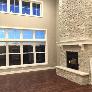 他の地域の中サイズのコンテンポラリースタイルのおしゃれなLDK (グレーの壁、標準型暖炉、石材の暖炉まわり、埋込式メディアウォール) の写真