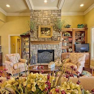 アトランタの広いトラディショナルスタイルのおしゃれなLDK (フォーマル、黄色い壁、無垢フローリング、吊り下げ式暖炉、石材の暖炉まわり、据え置き型テレビ) の写真
