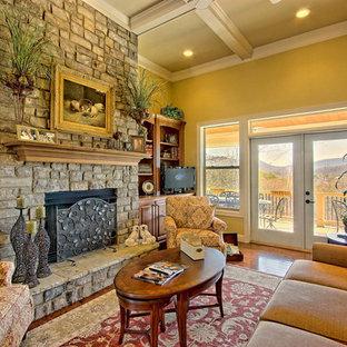 アトランタの大きいトラディショナルスタイルのおしゃれなLDK (フォーマル、黄色い壁、無垢フローリング、吊り下げ式暖炉、石材の暖炉まわり、据え置き型テレビ) の写真
