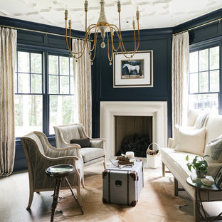 Example of a large transitional formal and enclosed light wood floor and beige floor living room design in Atlanta with blue walls, a standard fireplace, a plaster fireplace and no tv