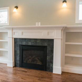 This is an example of a large arts and crafts open concept living room in Portland with beige walls, medium hardwood floors, a standard fireplace, a tile fireplace surround and a built-in media wall.